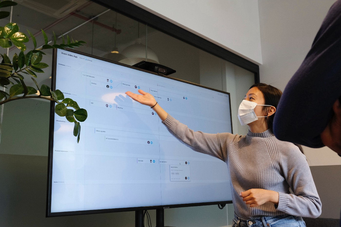A woman in a mask gesturing to a TV screen to showcase specific design elements.