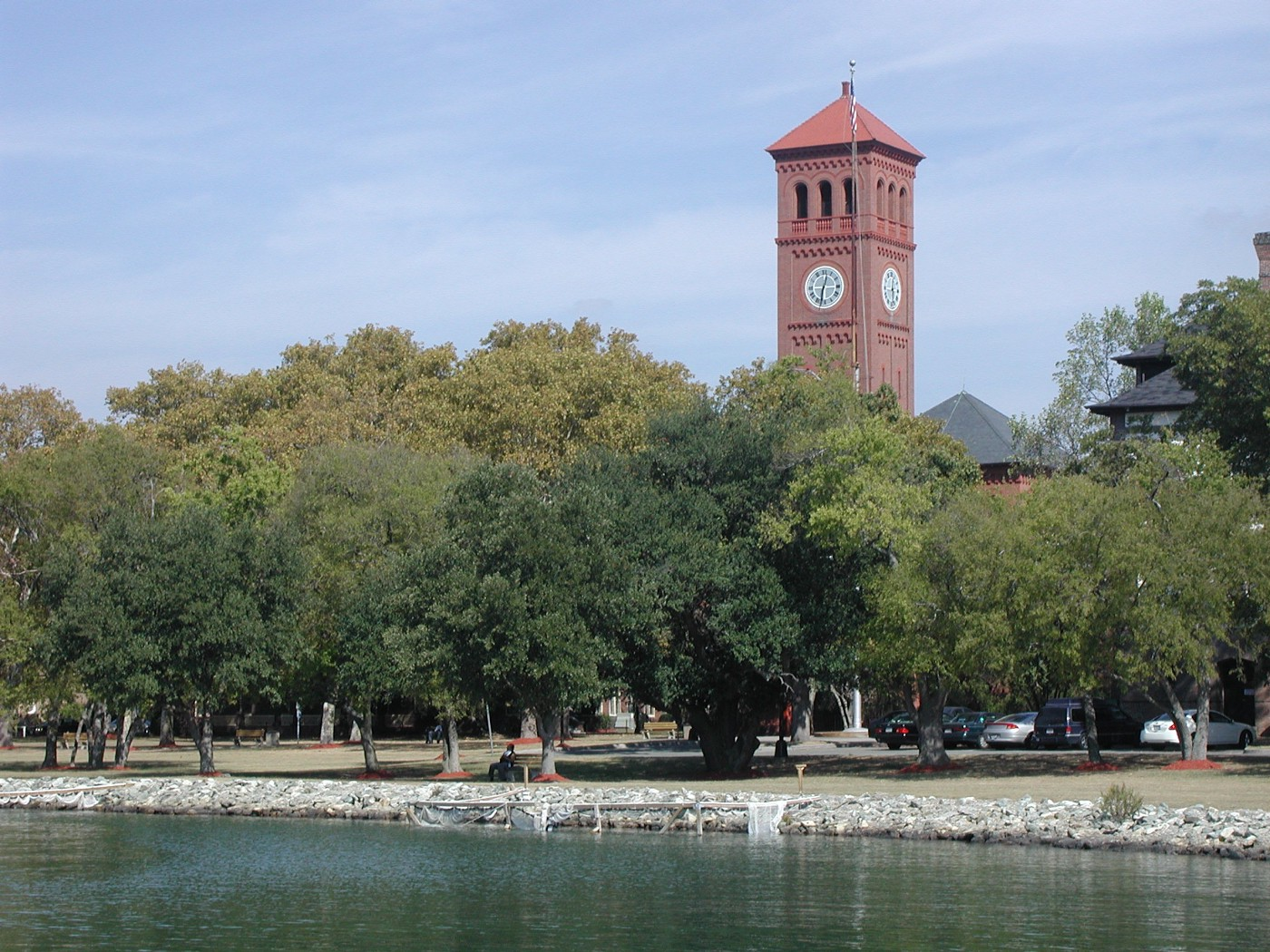 Clock tower and green trees on the waterfront