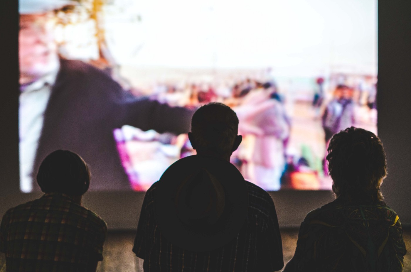 three people sitting and watching blurry bright images projected on a wall in front of them.