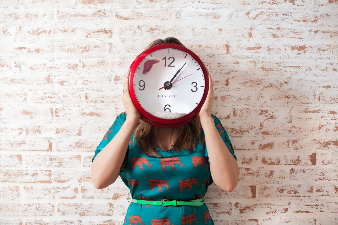 Woman holding a clock to cover her face