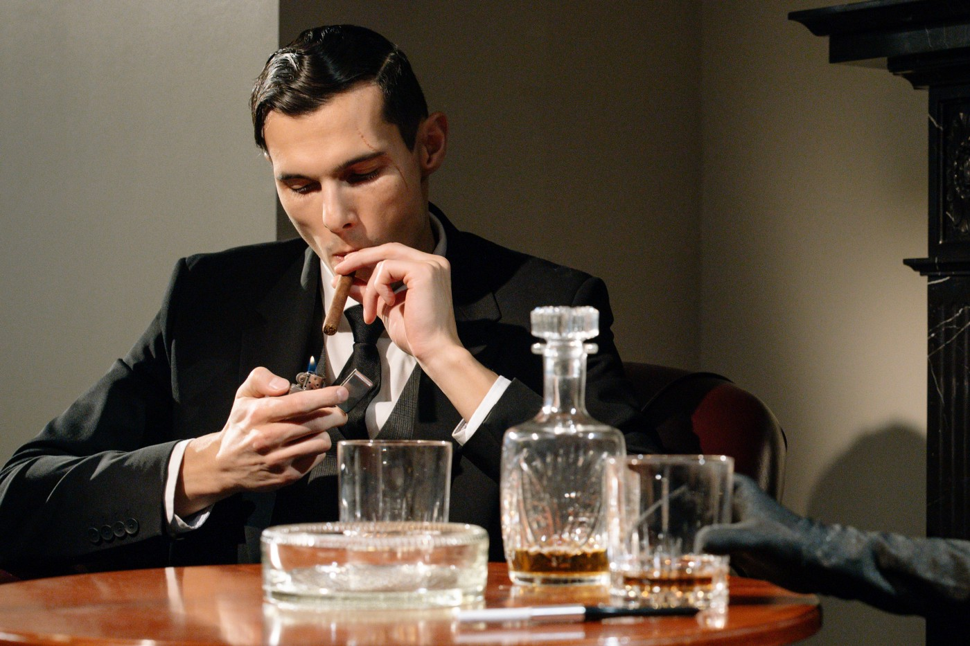 Debonair man lights a cigarette at a table with a whisky decanter and glasses on it.