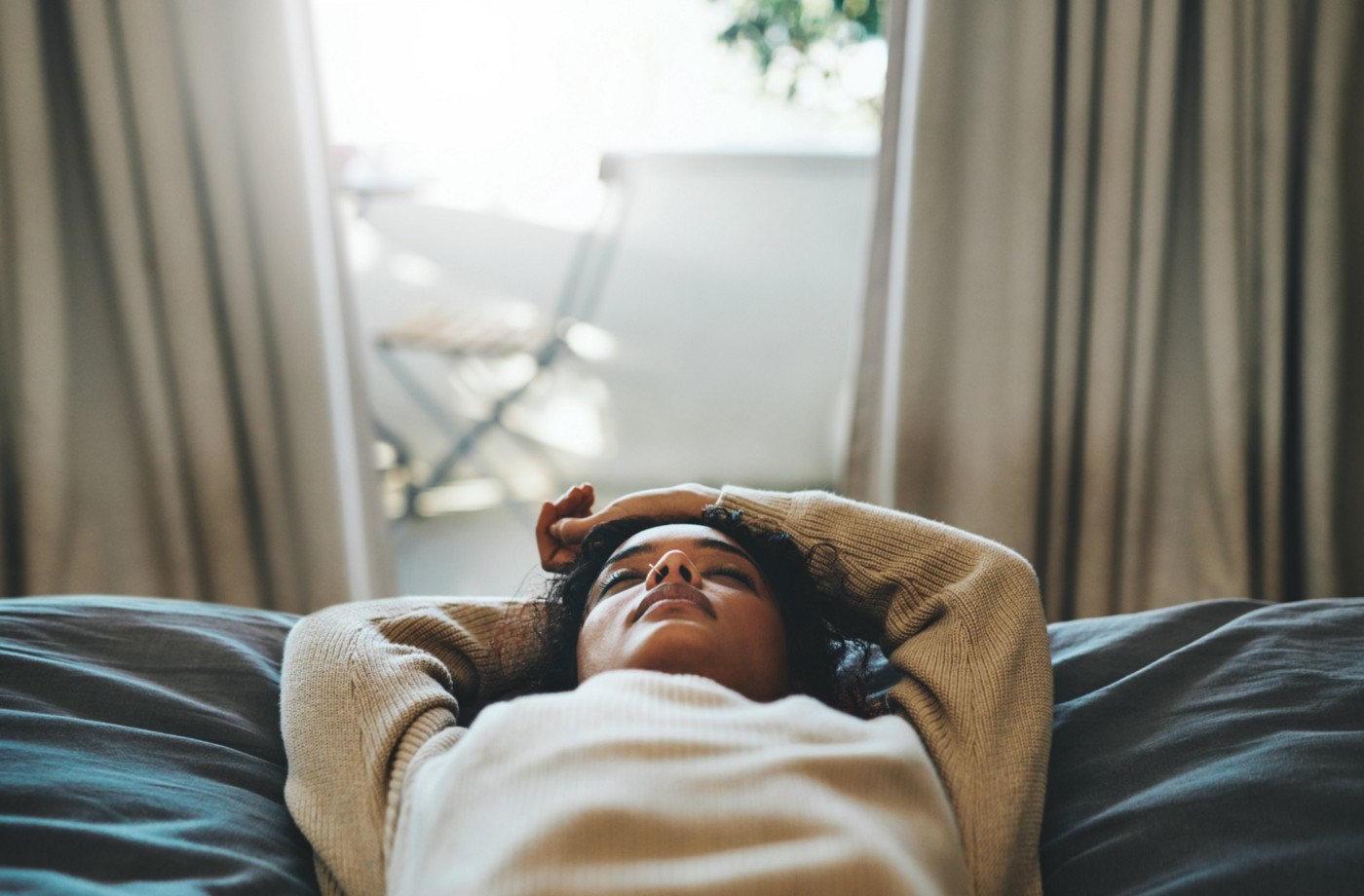 Black woman lying down with eyes closed.