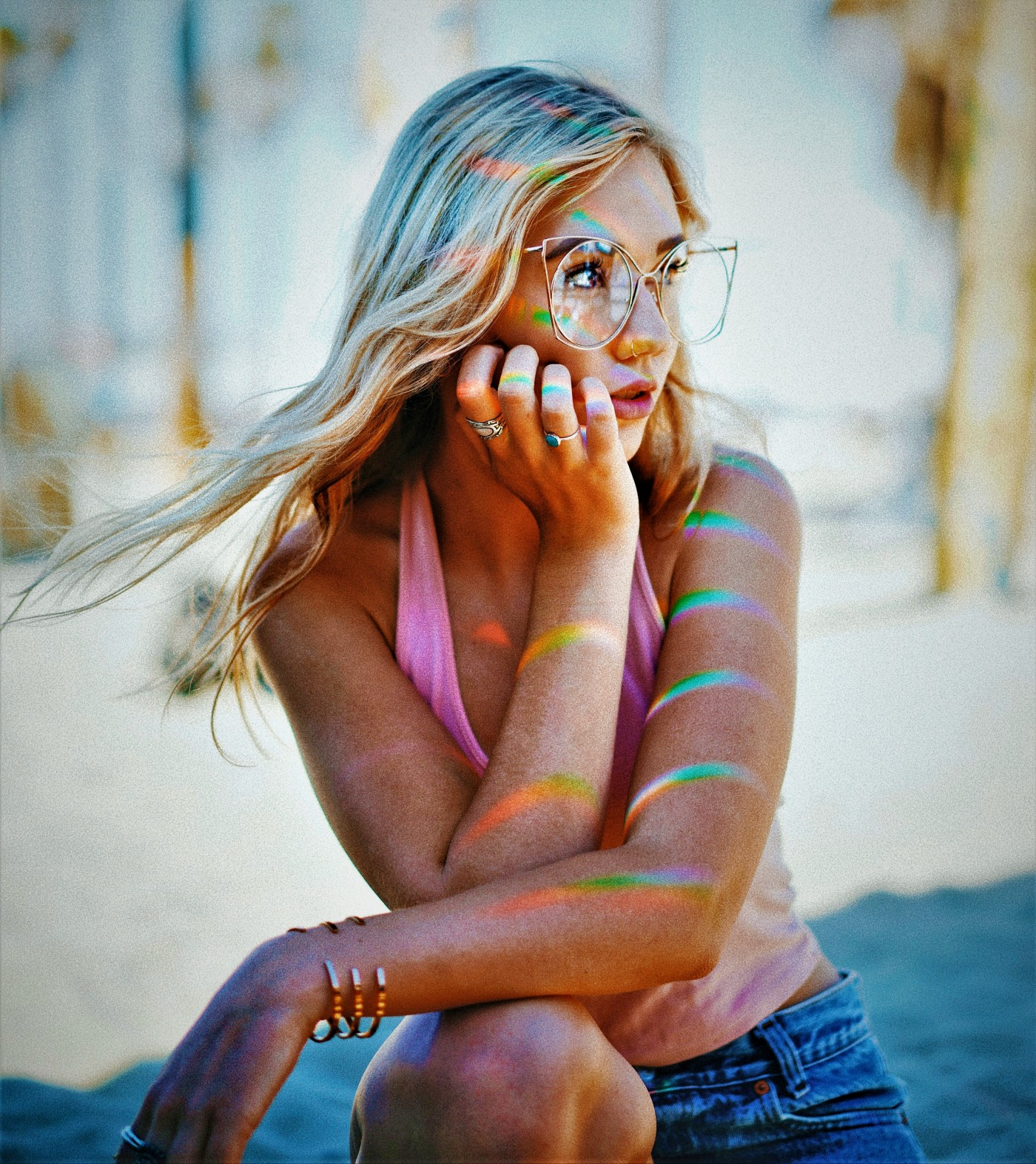 pensive girl with long blonde hair wearing glasses and pink top