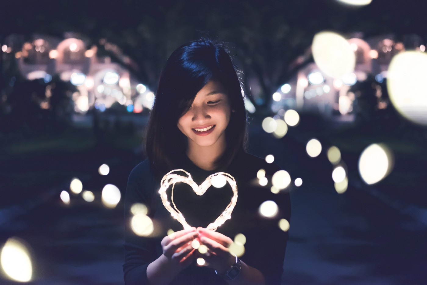 Asian woman holding up a wire heart with bright blobs of light behind her and lights in the darkness in the background