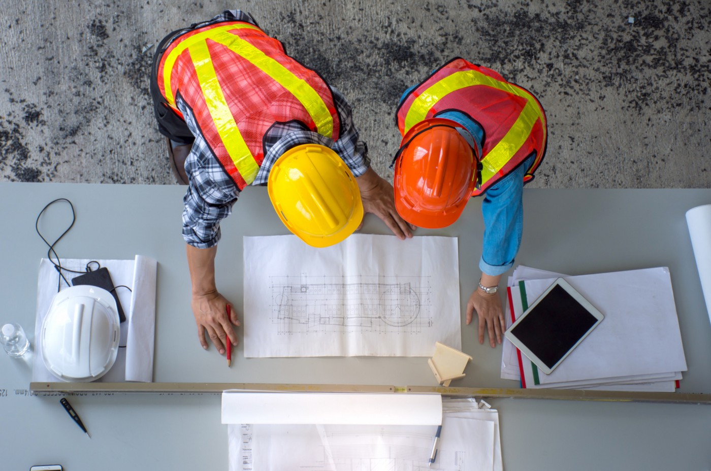 Two engineers with hard hats and safety vests on are looking at a blueprint that's spread out on a table.