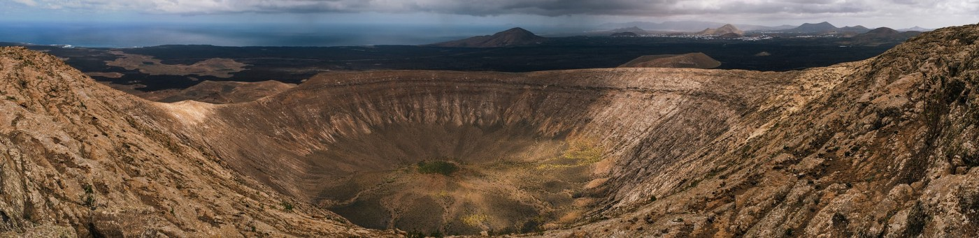 A vast, empty crater with distant mountains, ominous clouds and peeking sunlight in the background