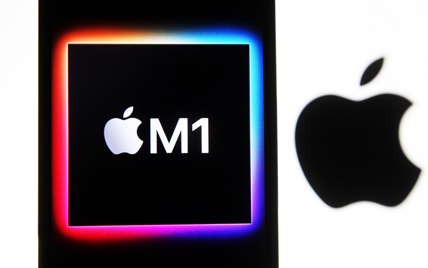 The Apple M1 chip computer logo seen on a mobile phone screen next to a larger Apple logo