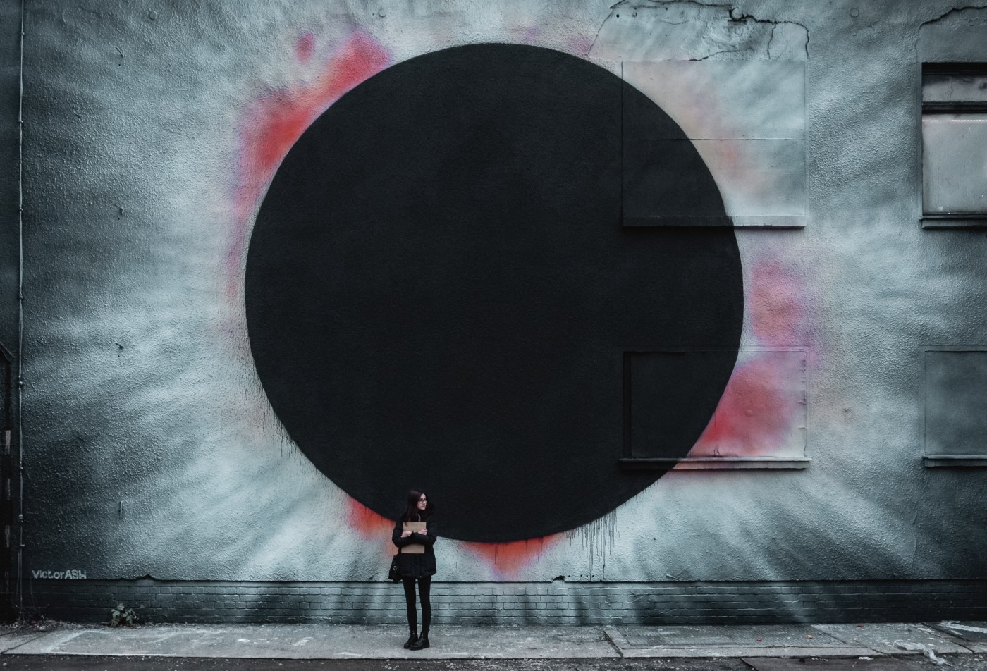 A girl standing in front of a gray wall painted with a large black circle