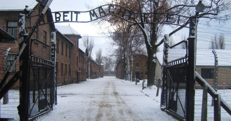 Image of the entrance to the Auschwitz Concentration Camp, snow blankets the ground