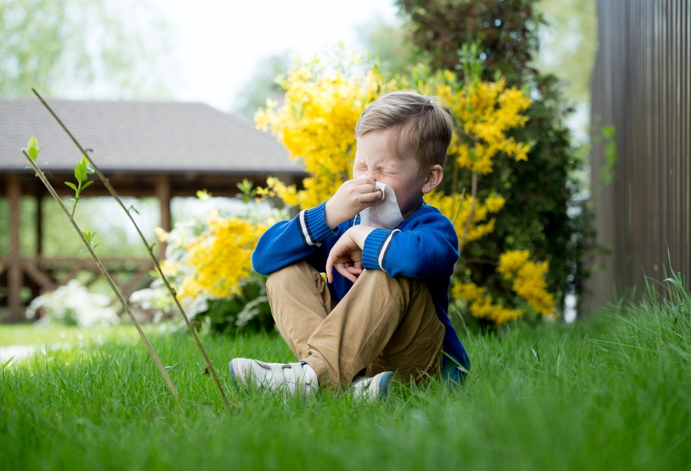 A boy is sneezing on the grass due to hay fever allergy.