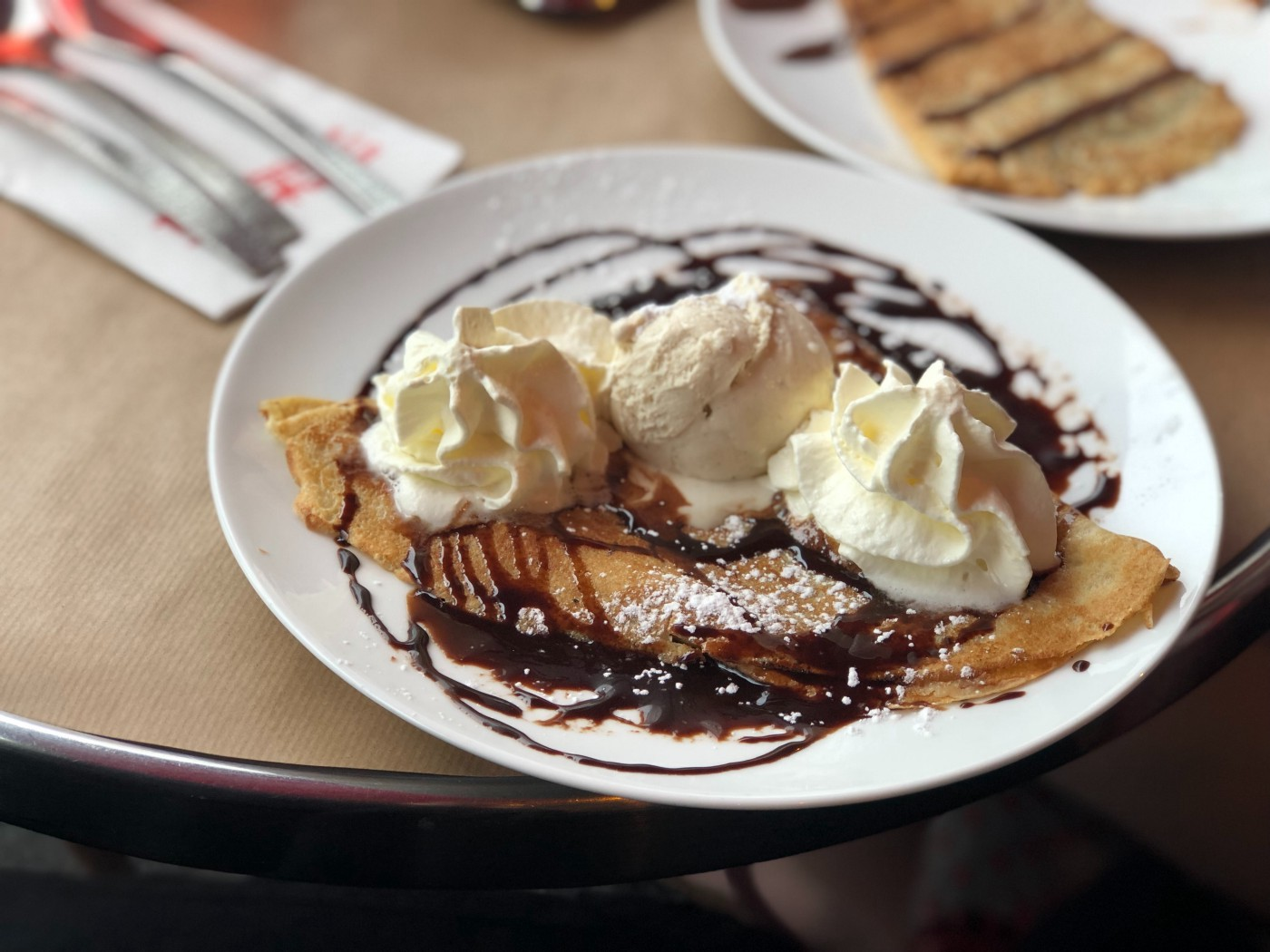 A crepe topped with chocolate sauce, ice cream, and whipped cream.