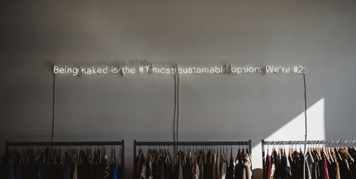"Photo of a wall with a lit up sign that reads: ""Being naked is the #1 most sustainable option. We're #2"" above clothing racks"
