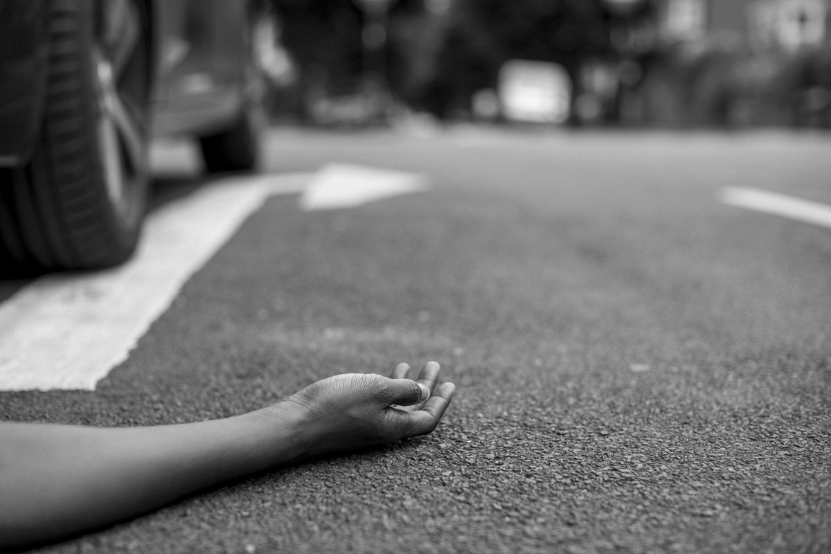 Person lying on road after a road accident