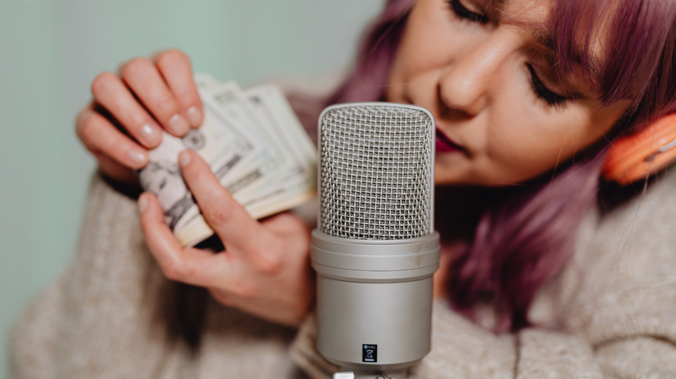 White woman with purple hair holds US dollar bills in her hands in front of a silver microphone