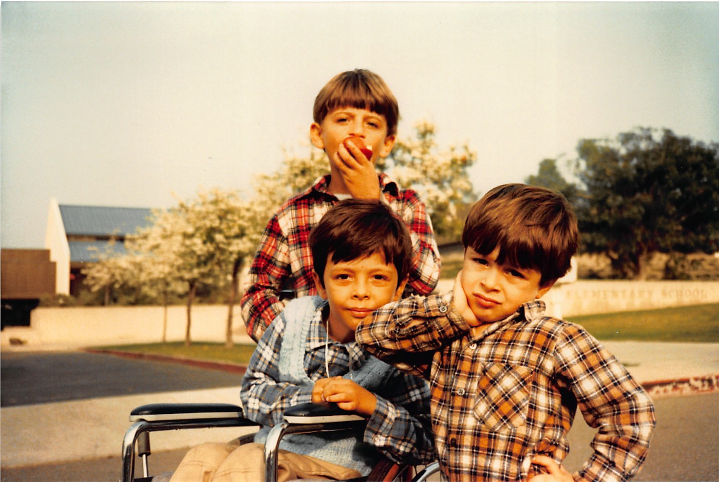 Description: This image shows three brothers wearing plaid shirts. The boy in the middle sits in a wheelchair in front of Roy