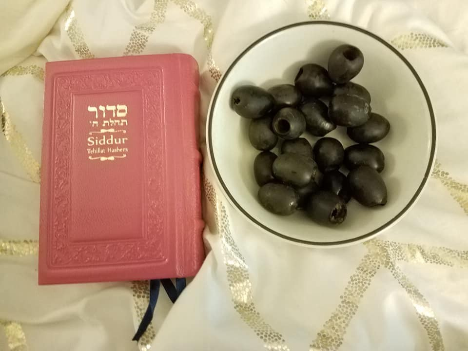 Pink Siddur Tehillat Hashem next to a bowl of olives on a gold and cream bedsheet.