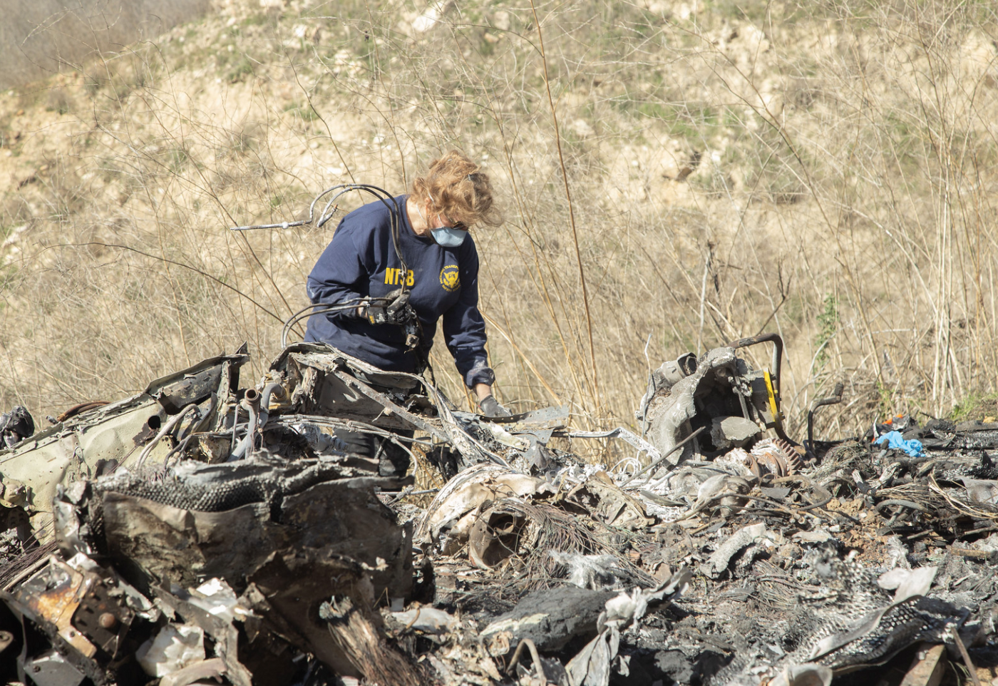 NTSB investigator Carol Hogan examines the wreckage of the helicopter involved in the crash that killed Kobe Bryant