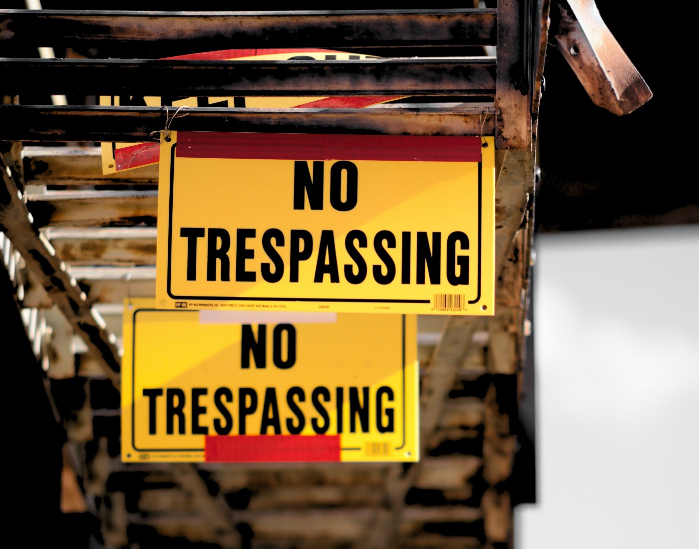"Two black on yellow ""No Trespassing"" signs"