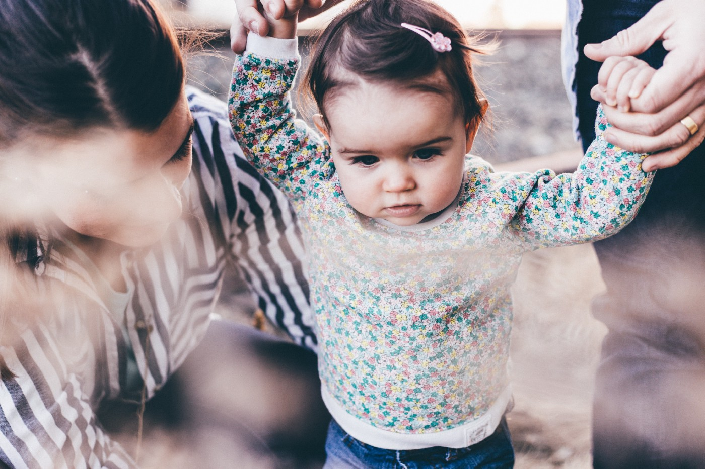Toddler learning to walk holding parent's hand