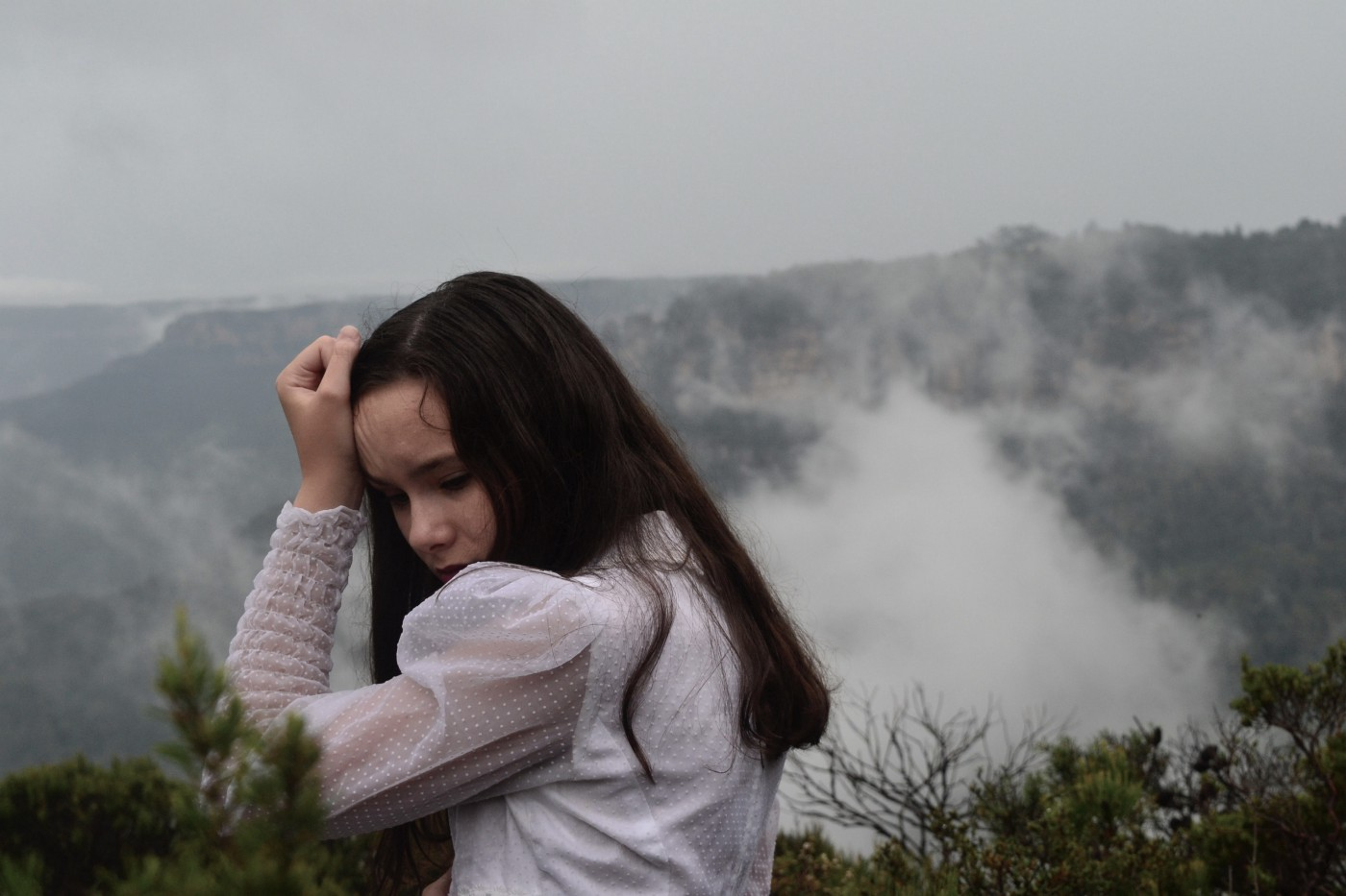 a young woman with long dark brown hair, looking sad with a white shirt, holding up her arm with her head tucked into her arm, with a cloudy background and some bits of dark green foliage in the foreground