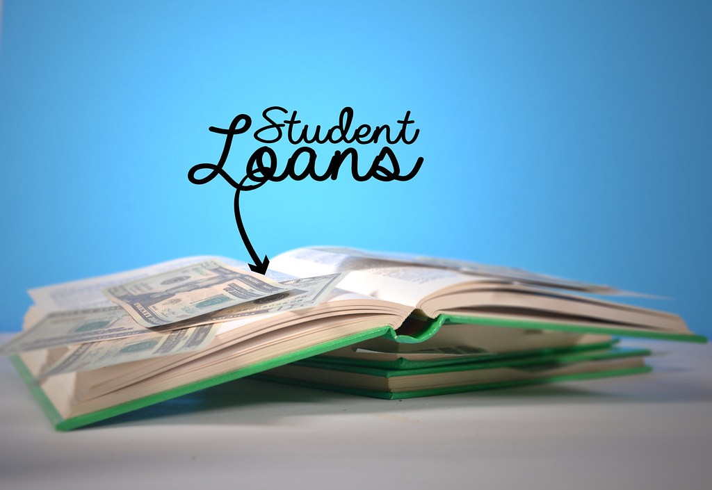 open book with dollar bills spilling out. the title reads student loans.