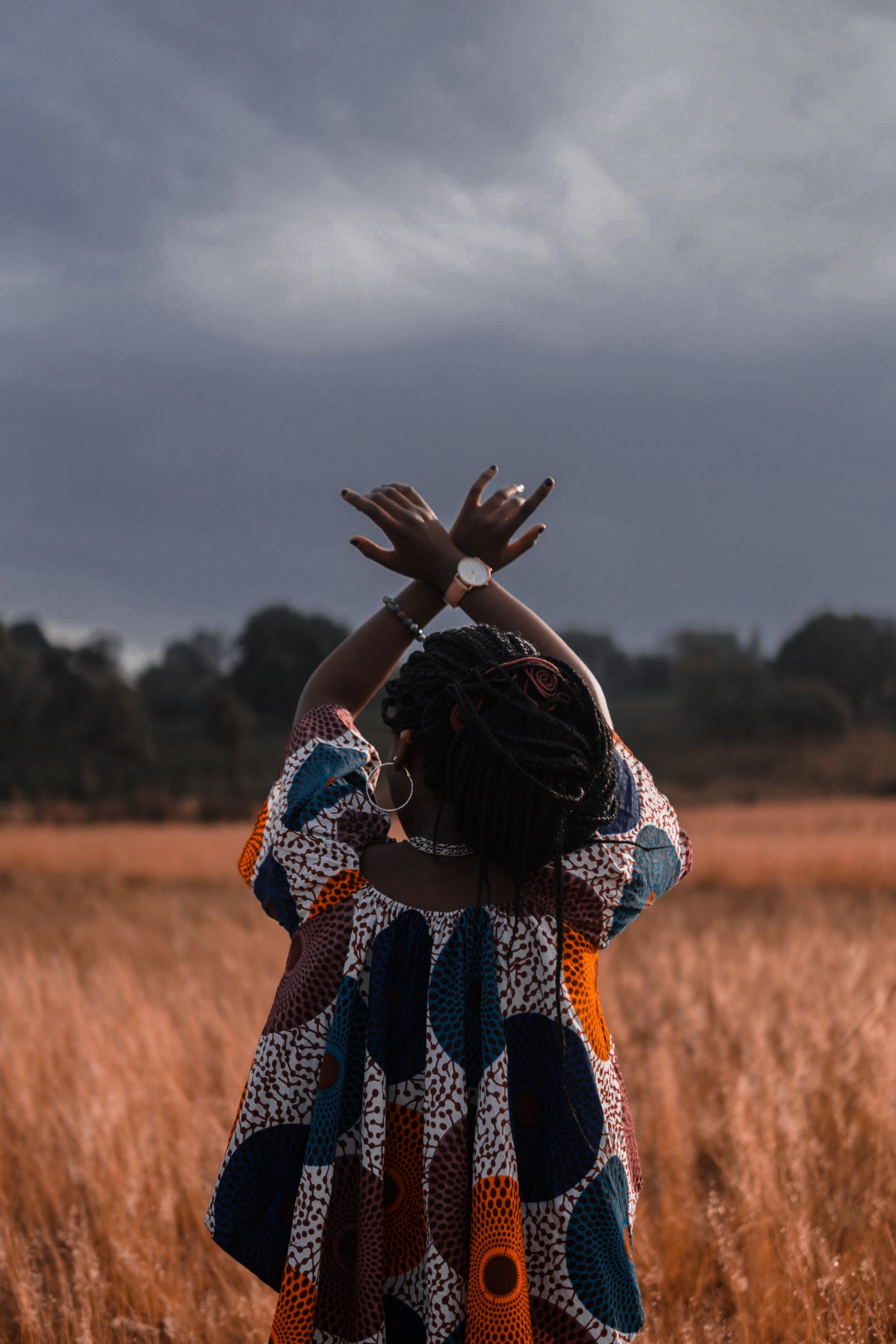 Black womxn with braids in African print dress, back to camera, hands up towards a grey sky.