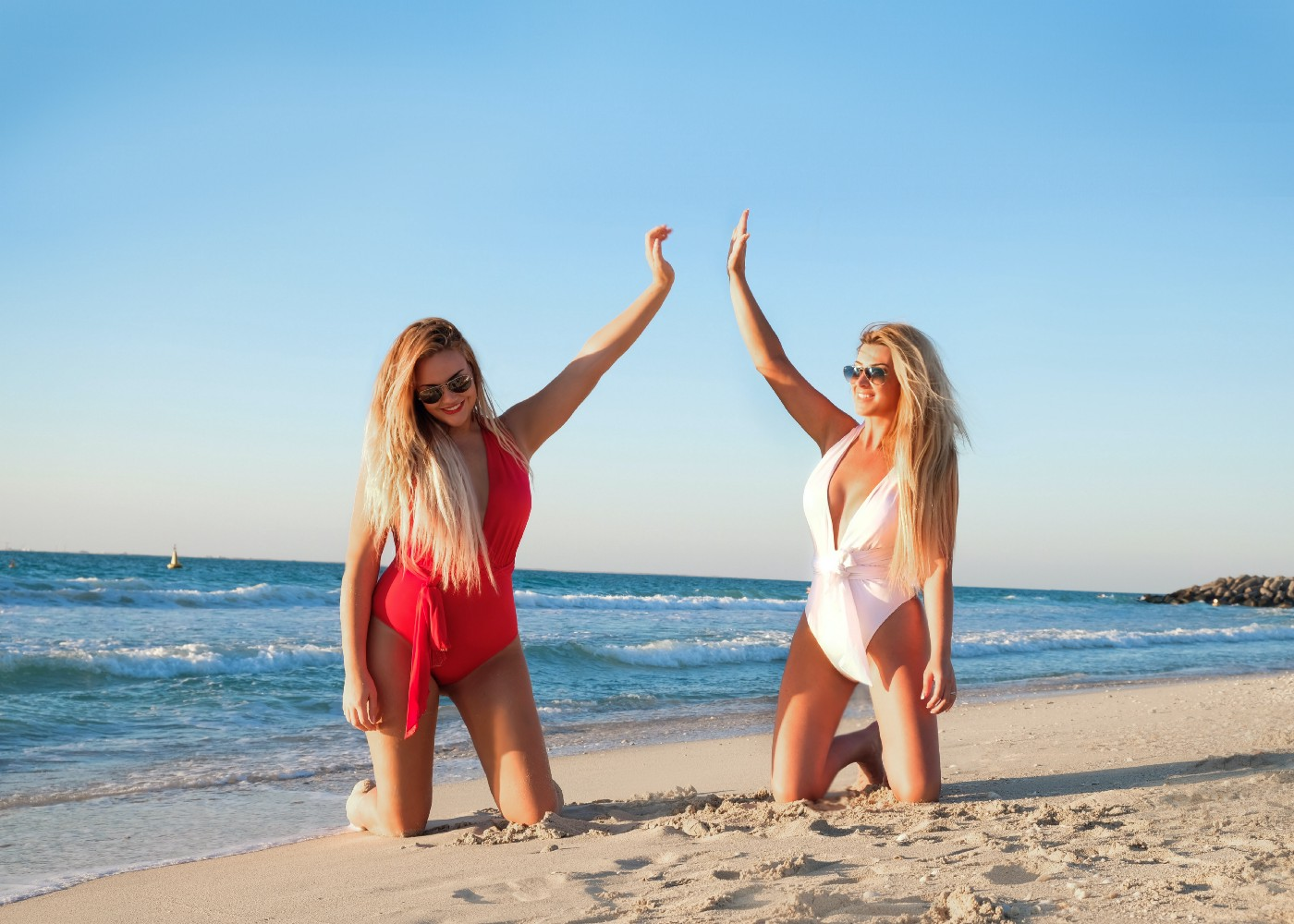 Two beautiful women on the beach about to high five each other.