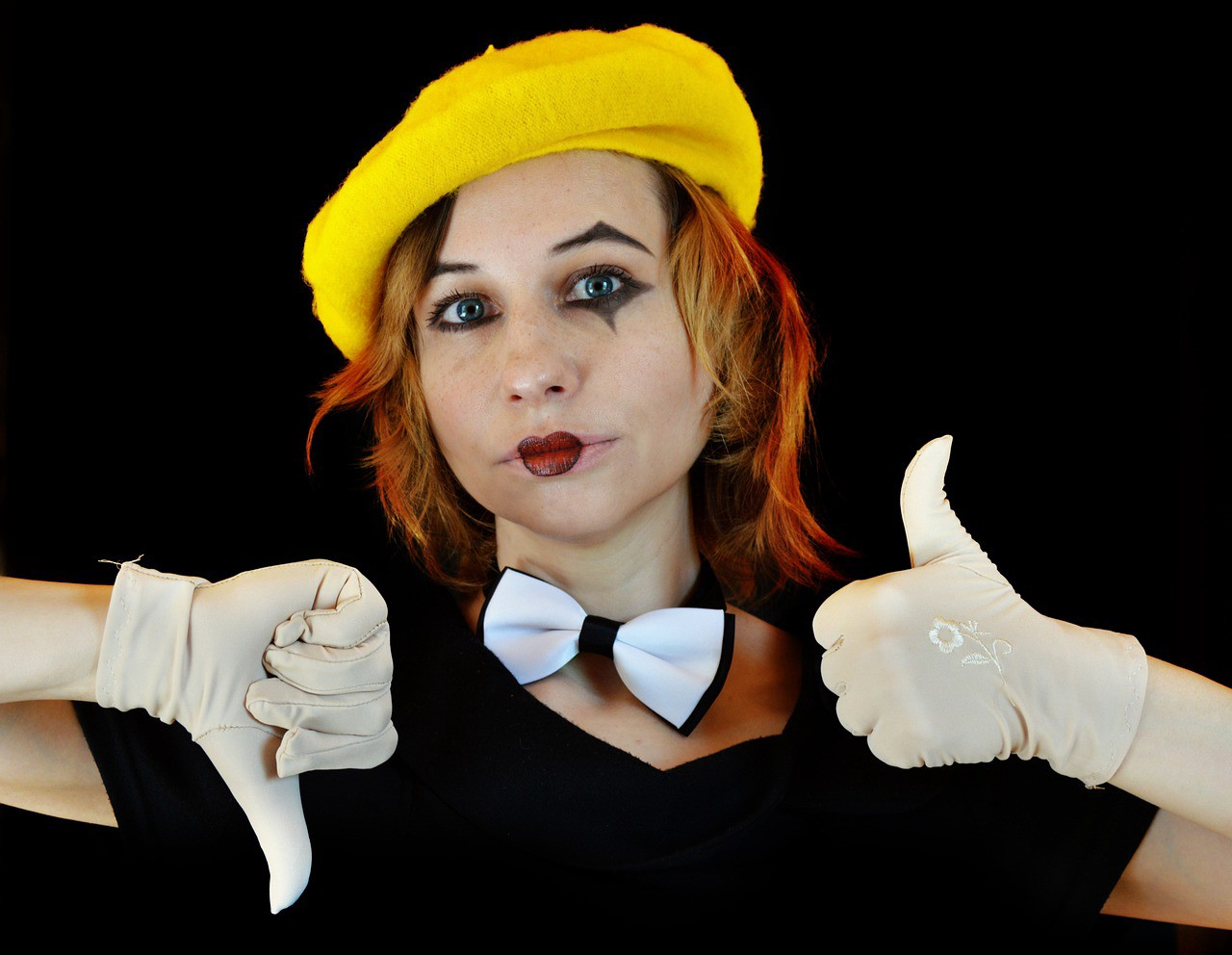 A mime woman in white gloves with thumbs up and thumbs down.
