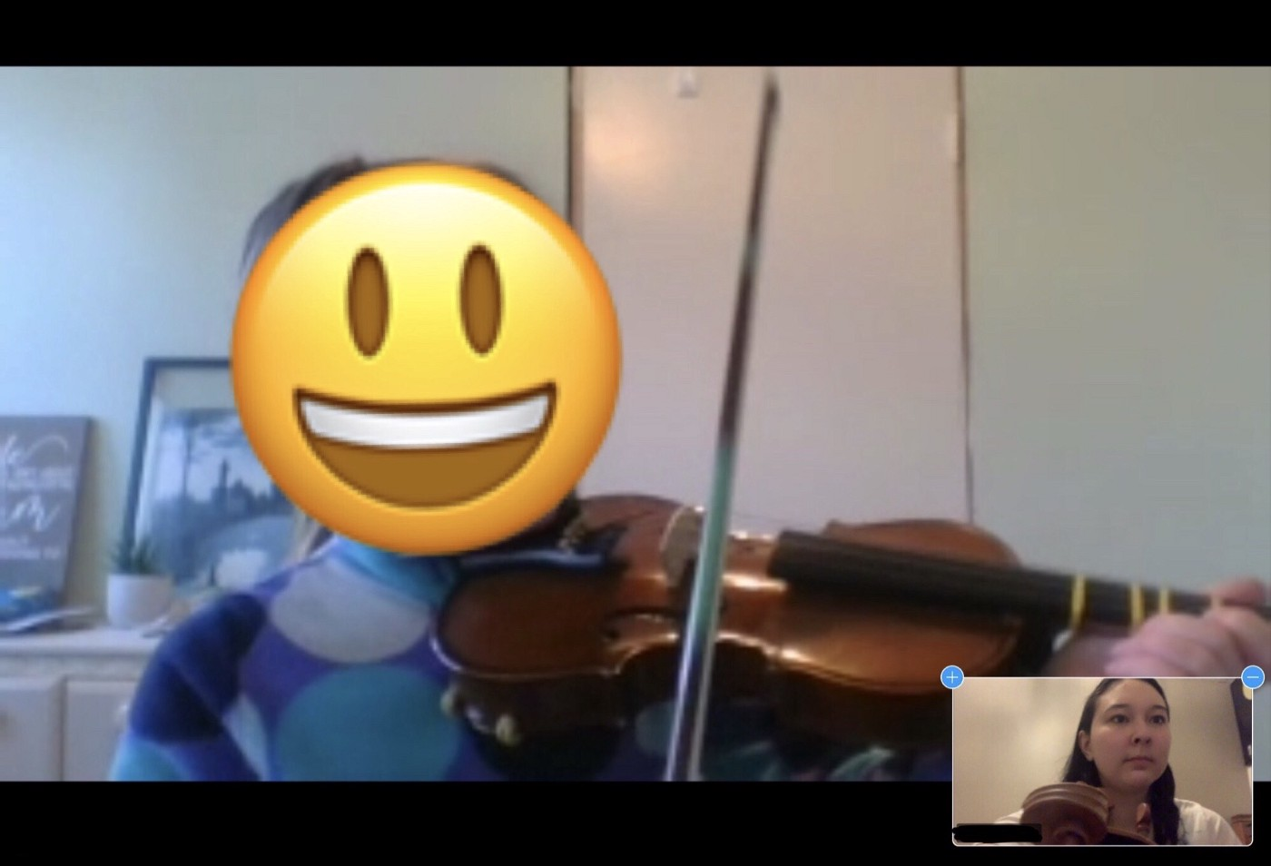 Screenshot of a Zoom call. The author is teaching a young violin student who's face as been blurred for privacy/safety.