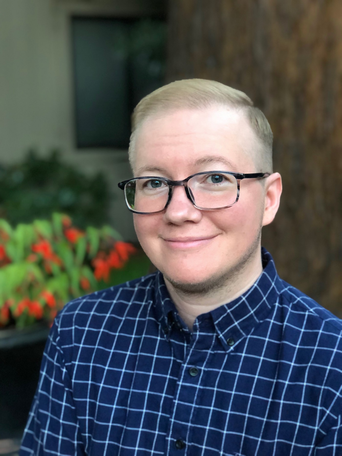 A photograph of AJ Sass, a white male-presenting person in a checked blue shirt. AJ has large glasses, light, short hair shaved on the sides, slight facial hair stubble, and a gentle smile.