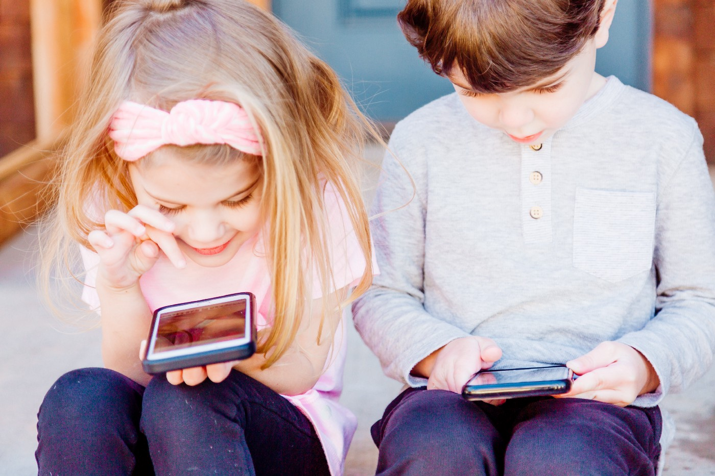 Photograph of two children playing on mobile devices