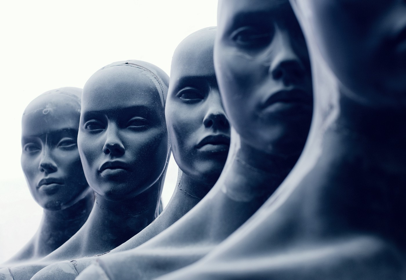 A photo of five sculpture-like human faces.