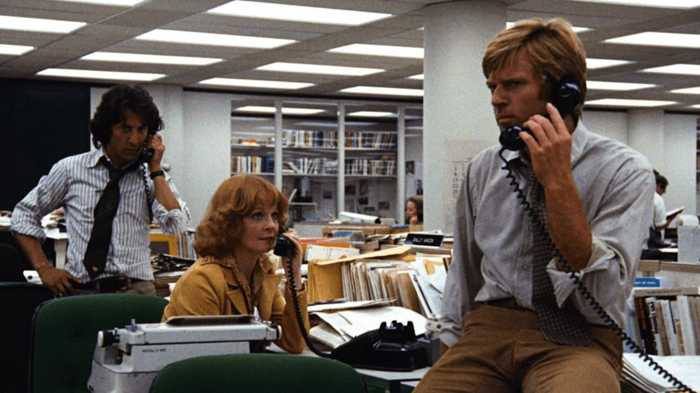 Still from the movie All the President's Men. Two men and one woman in a newsroom, all on the telephone.