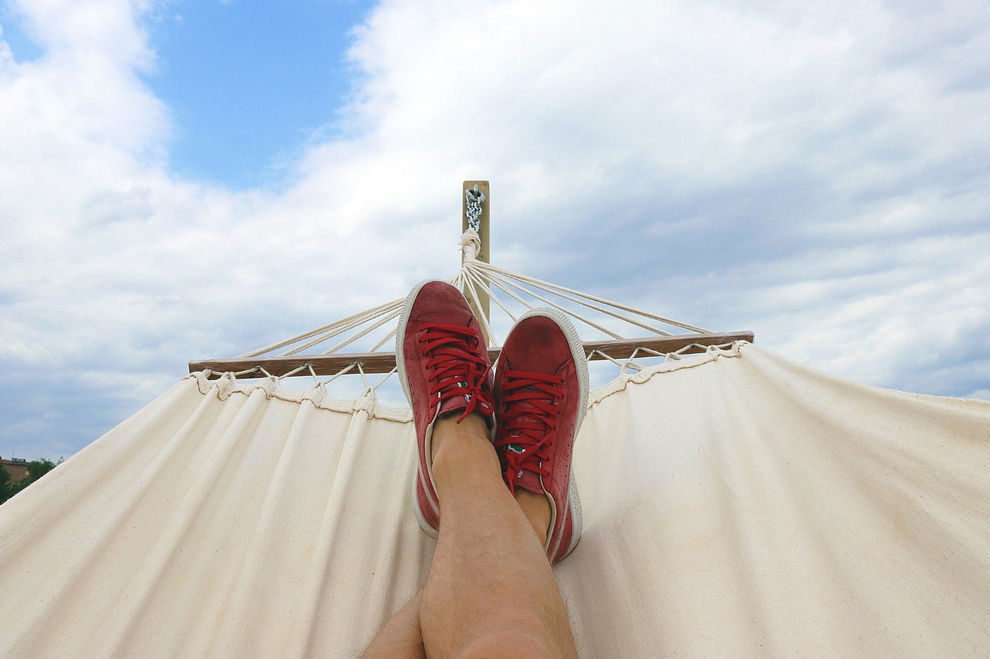 man-relaxing-in-hammock-with-red-sneakers-blue-cloudy-skies