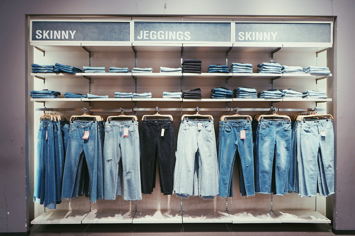 "A rack of jeans in a store, with signs above that say ""Skinny,"" ""Jeggings,"" and ""Skinny"" again."