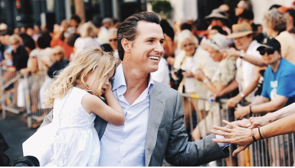 Governor Gavin Newsom of California greets voters while carrying his daughter in the times before COVID.
