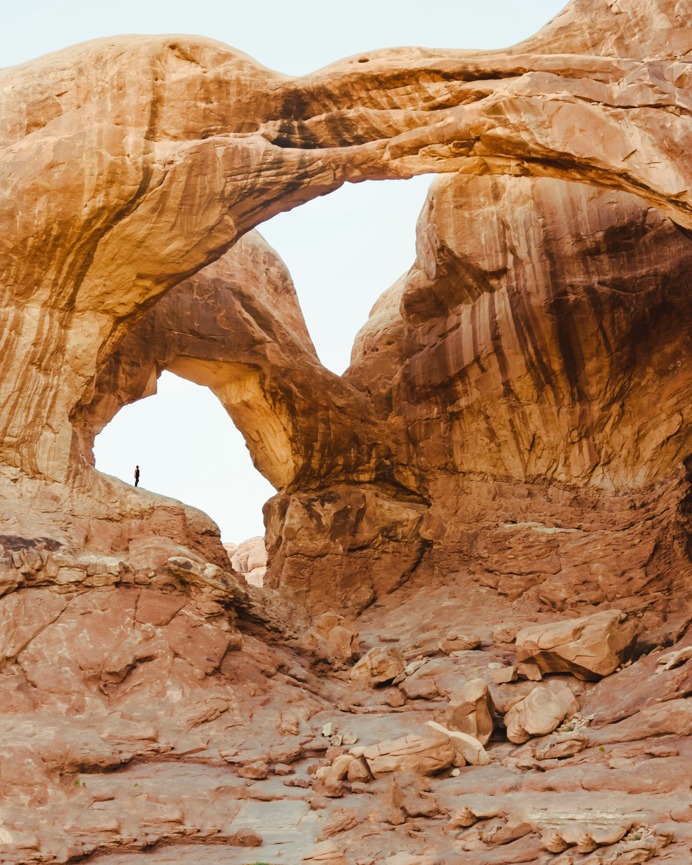 A hiker is standing on a slab of rock looking up at a giant stone arch in Moab, Utah