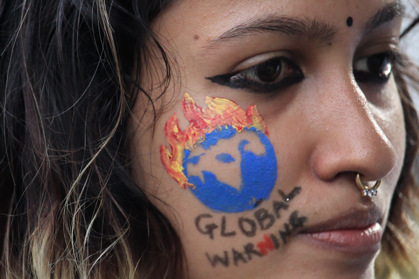 """A close-up of a woman's face with a painted drawing that says """"Global Warning."""""""