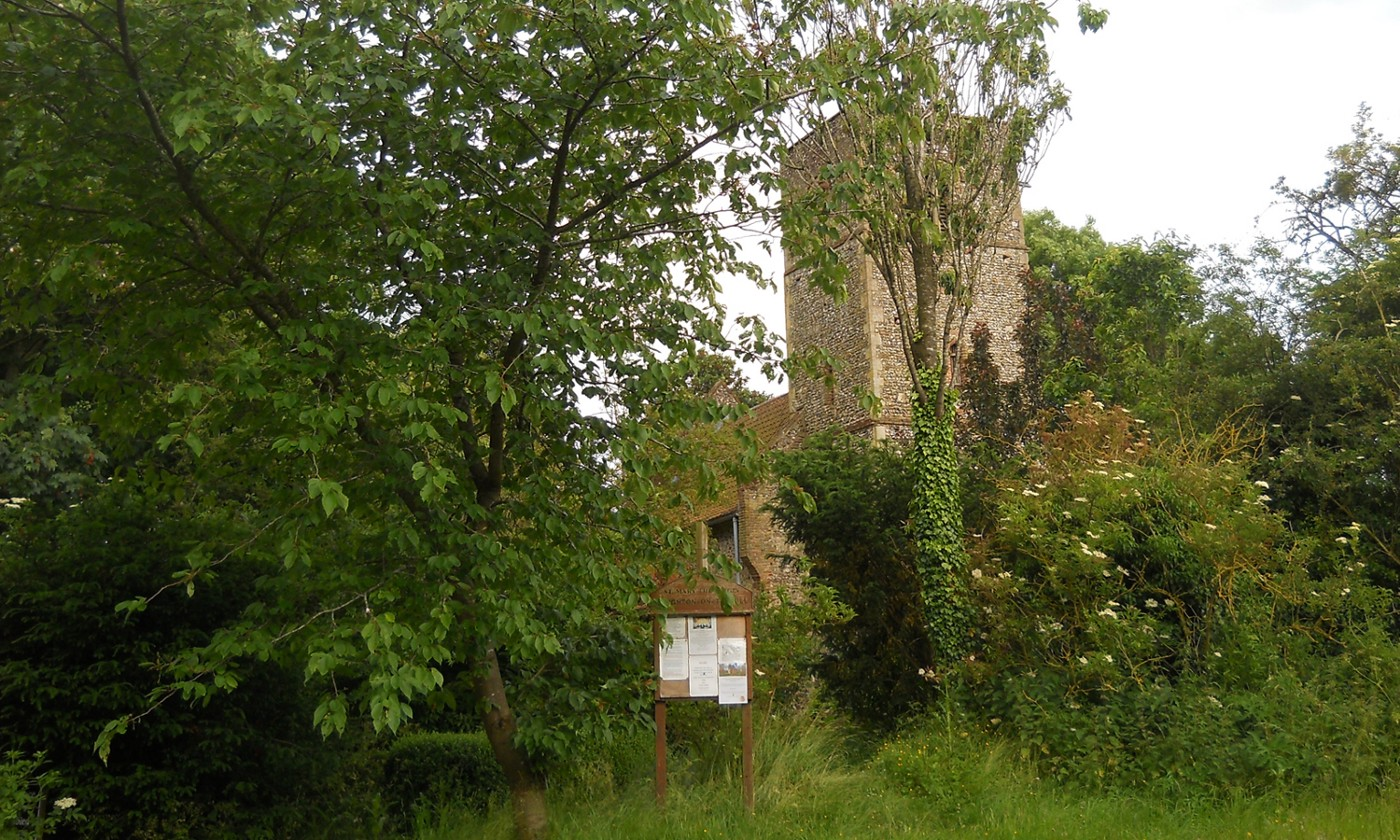 Square tower of a British medieval church hiding behind trees