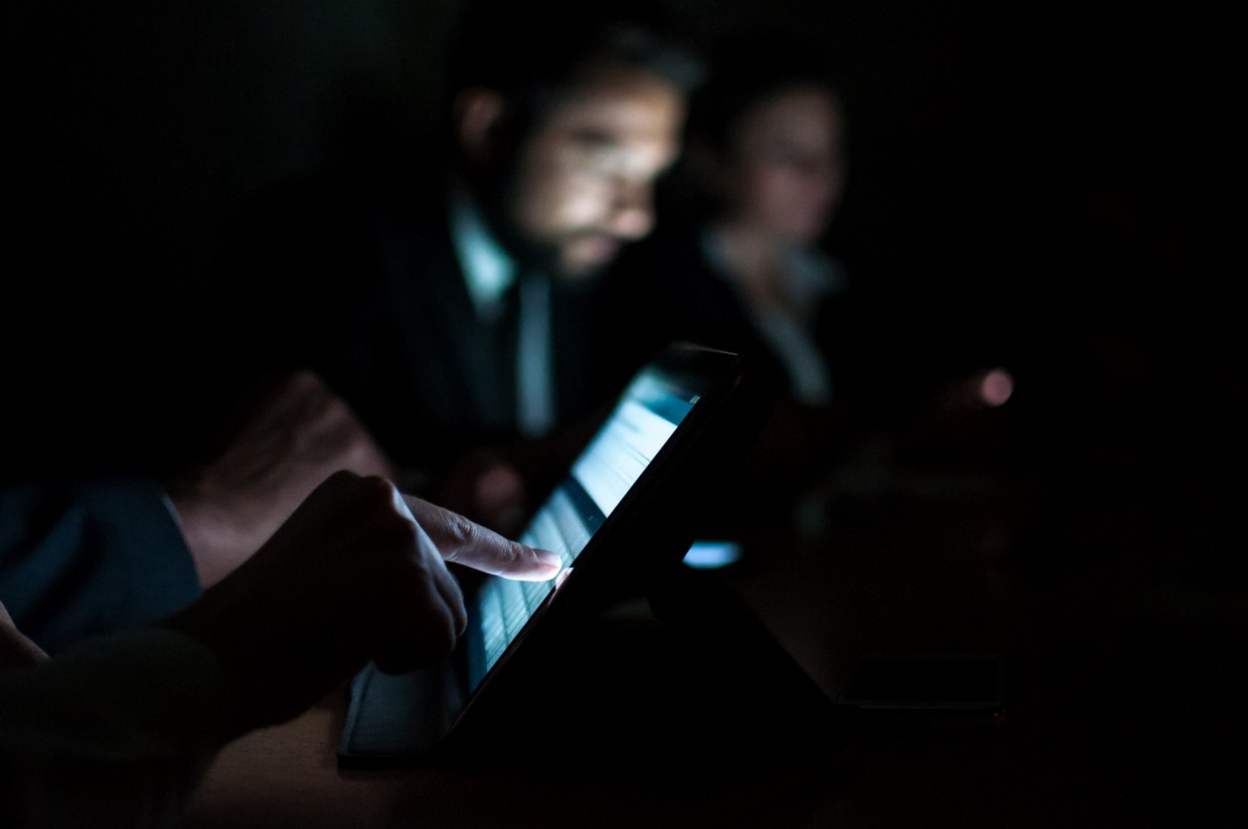 Dark photo of tech workers on tablets.