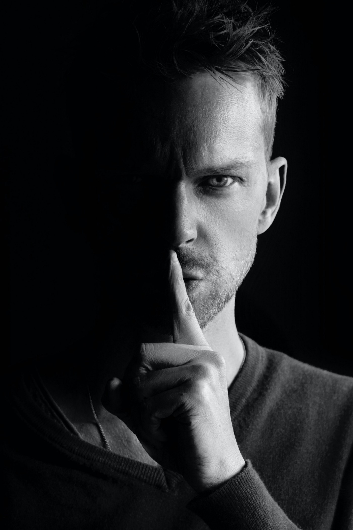 A dangerous-looking man in black and white trying to hush the viewer with a single finger.