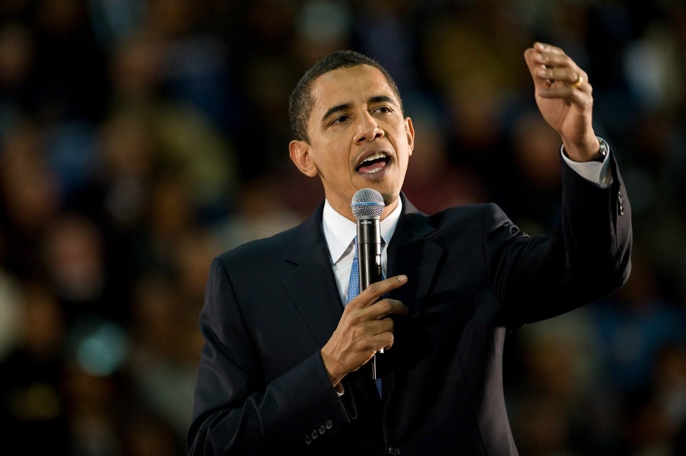 President Obama holds up microphone while delivering remarks to crowd.