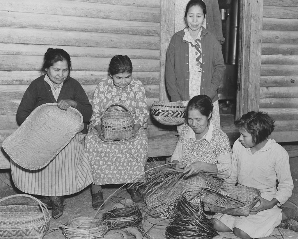 A black and white vintage photo of Choctaw women weaving baskets in the early to mid 20th century.