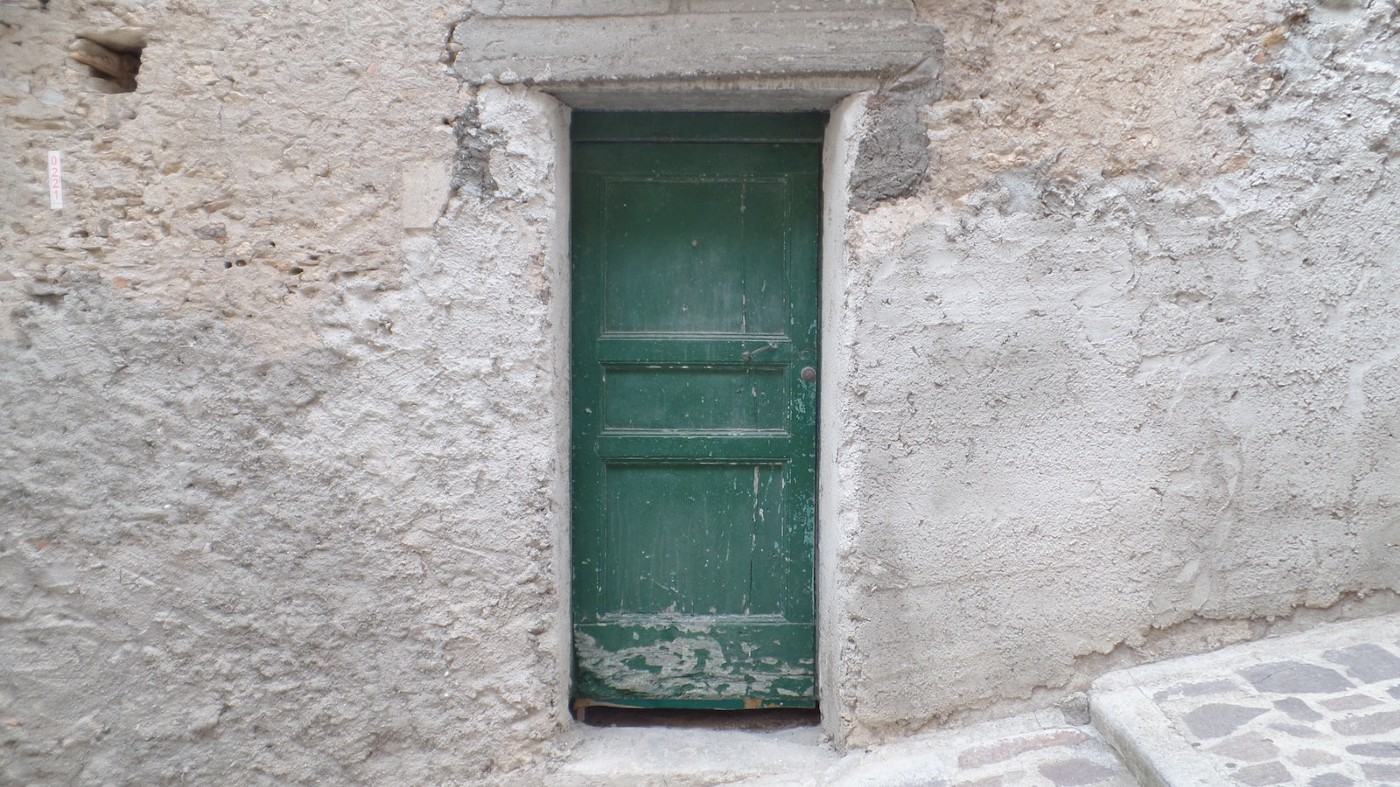 A faded green door in the middle of a stone wall