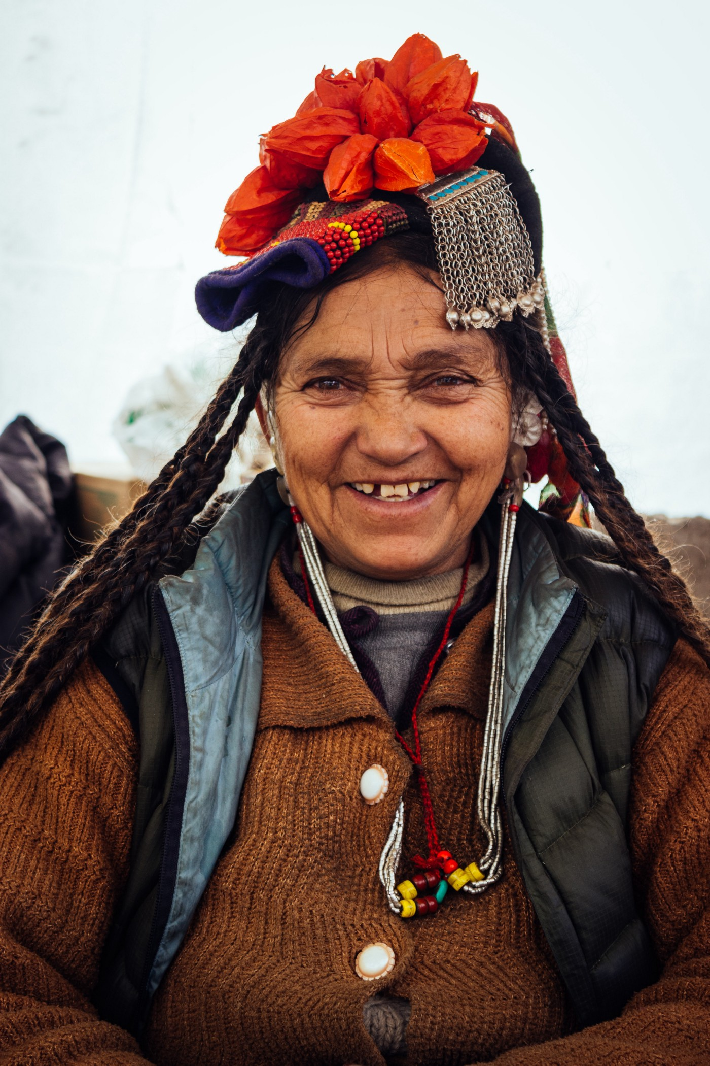 An old woman wearing a traditional dress and smiling.