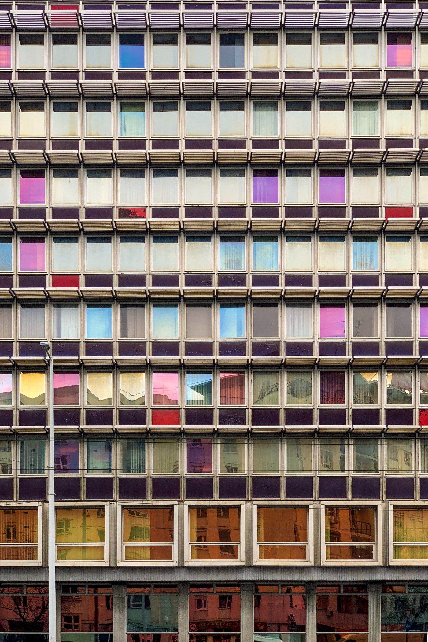 Windows on a block of buildings with different colors.