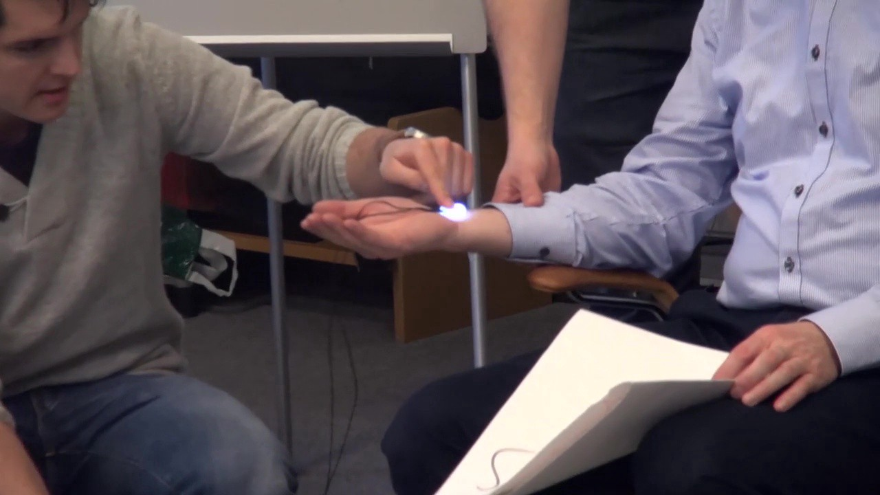 An illuminating device is placed on someone's wrist by another person.