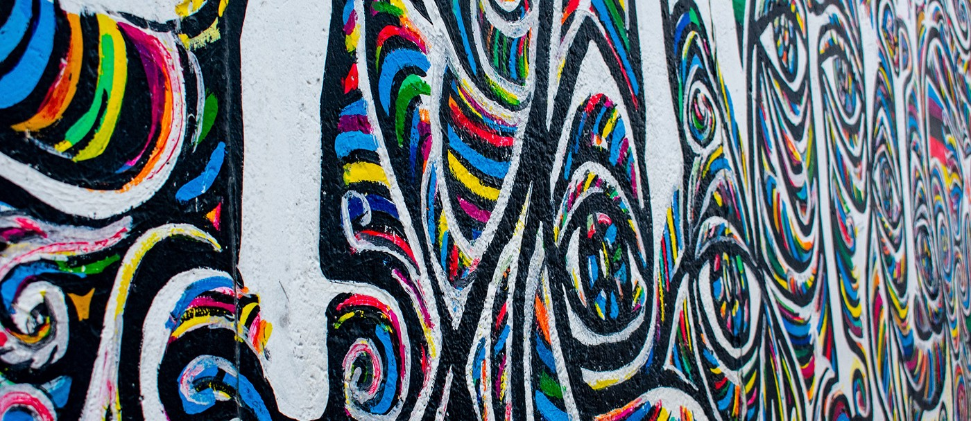 Graffiti showing an abstract image of bands of colour mixing and crossing paths