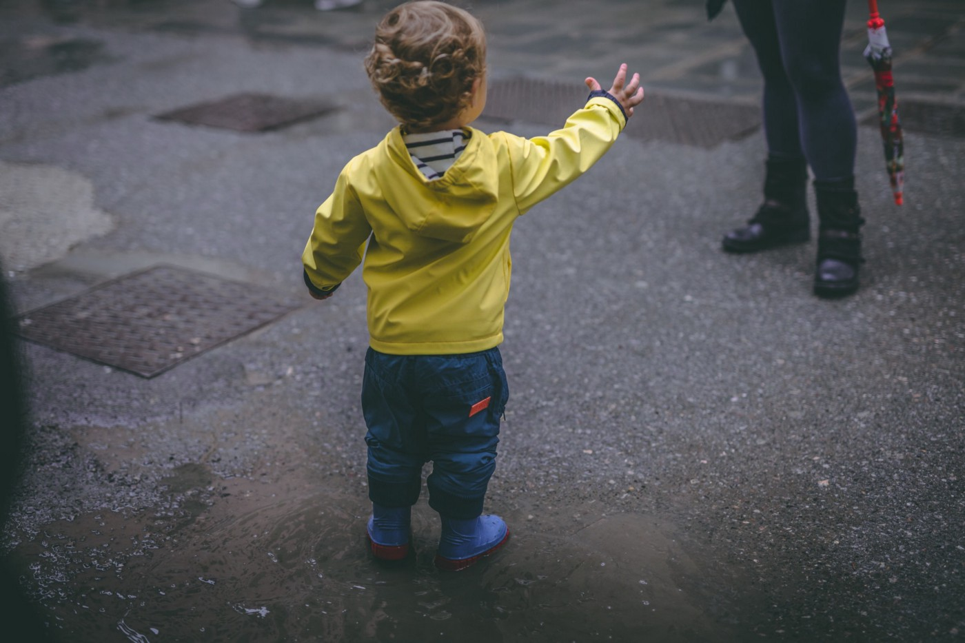 Toddler in yellow rain jacket reaches out for his mother