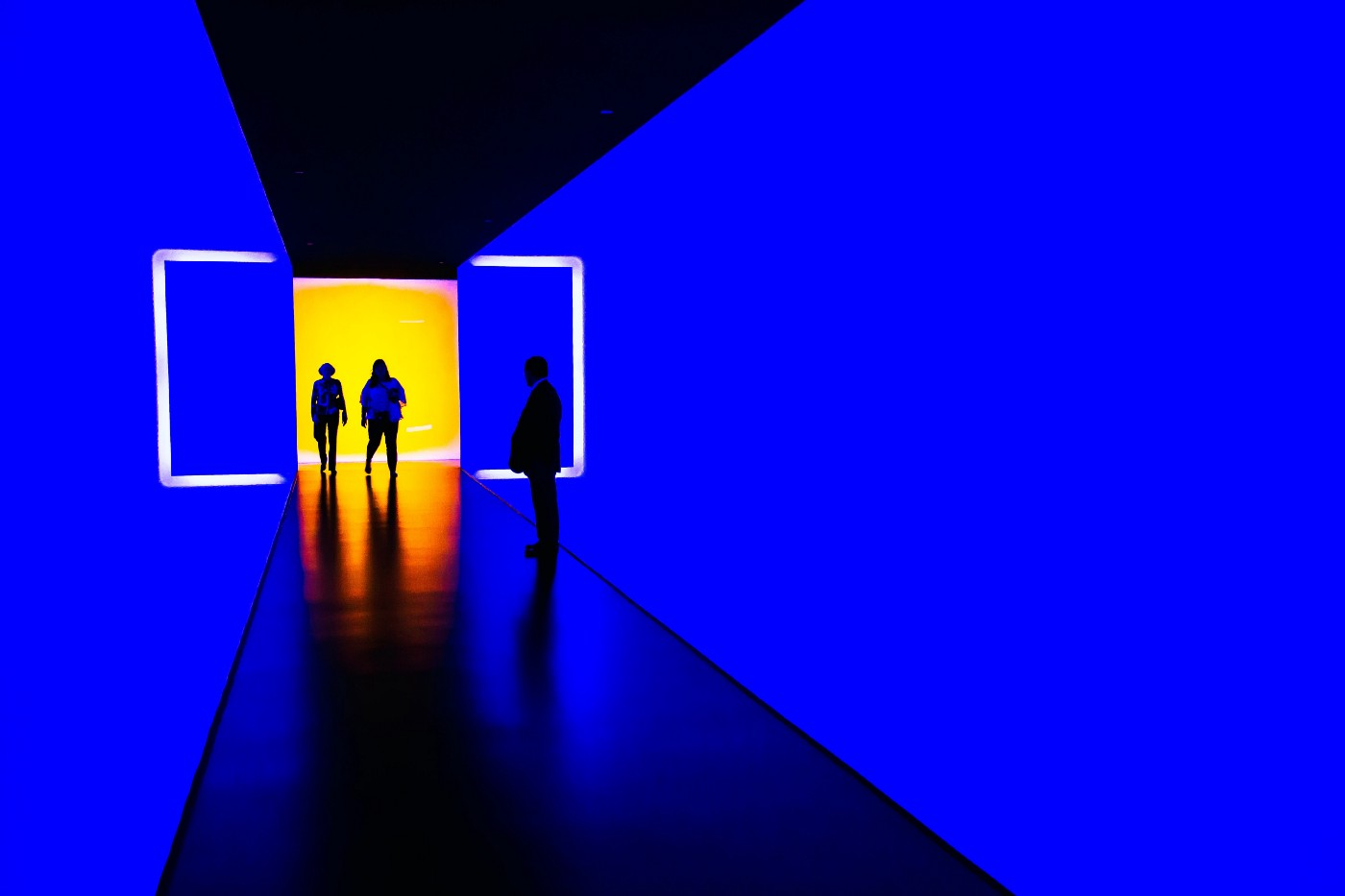 A futuristic blue hallway with people standing in it.